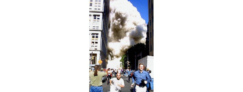 Une tour vient de s'effondrer, les gens fuient le nuage de poussière.
